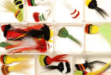 A plastic box of handmake fly fishing lures.
