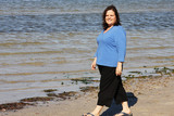 Beautiful plus sized model taking a relaxed stroll on  beach.