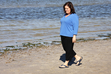 Beautiful plus sized model taking a walk by the sea.