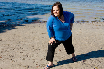 Beautiful plus sized woman working out on the beach.