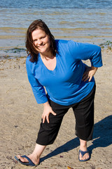 Plus sized woman stretching as part of fitness program.