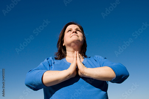 Woman praying outdoors against a vivid blue sky.