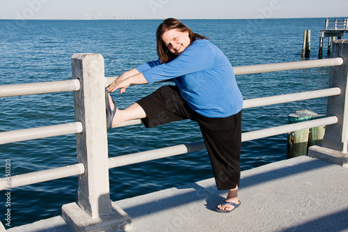 Beautiful plus-sized woman stretching on a fitness walk.