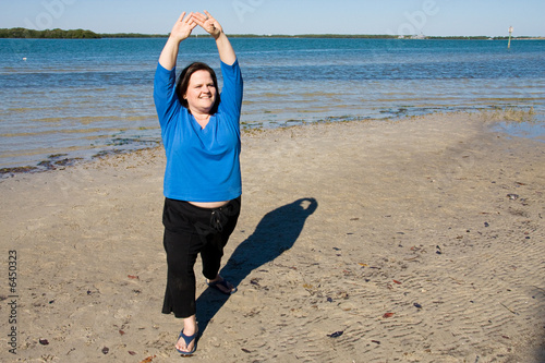 Beautiful plus sized model stretching out on the beach.
