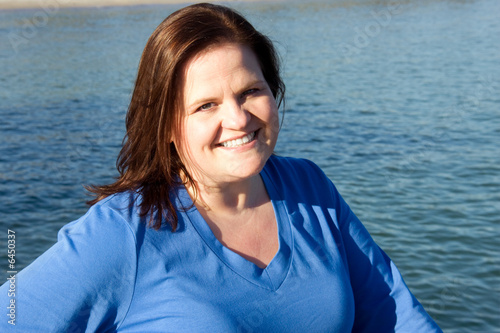Beautiful plus-sized model posing by the water.