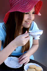 pretty girl wearing red hat and sipping tea