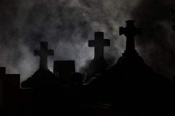 Headstone cross in Graveyard at night.