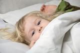 face of little blonde grey-eyed girl under blanket in bed poster