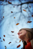 young woman looks up into fall sky as leaves fall around her