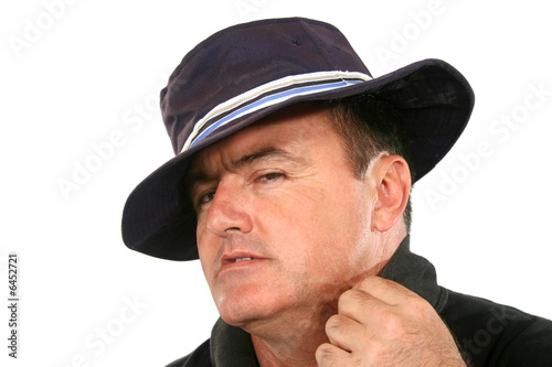 Man in hat with a suave and cool look.