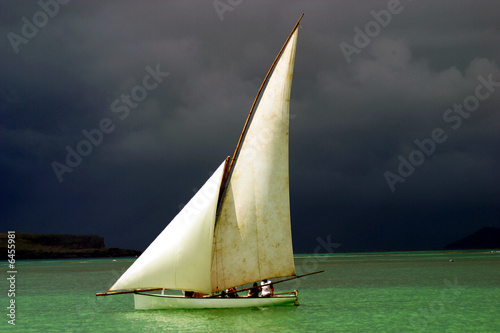 White sailed pirogue in front of dark clouds