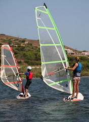 Instructor teaching child to windsurf