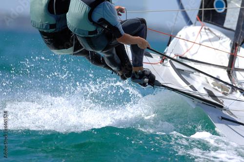 Sailors splash through the waves during a regatta. - 6465574