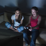 two young girls sitting on a couch playing video game poster