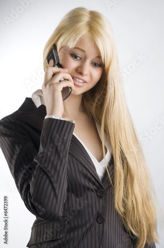 nice portrait of blond formal dressed woman talking with mobile