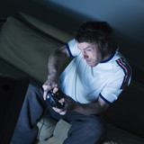 man sitting on a couch   playing video game poster