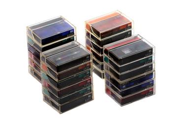 Four piles of mini-dv casette tapes, over white.