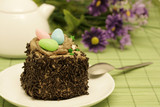 Colorful sweet eggs on a chocolate cake with sprinkles poster