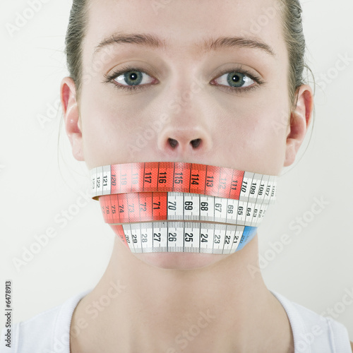 young beautiful caucasian woman gag by a meter ribbon