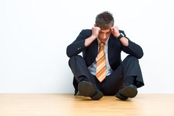 Unhappy businessman sitting on floor
