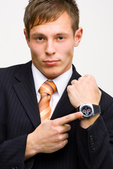 Angry young businessman showing his watch..
