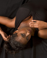 Portrait of beautiful black girl lying on back