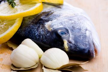 Roher Fisch mit Knoblauch, Lorbeerblätter und Zitrone