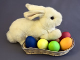 White rabbit sits on the wattled basket full of easter eggs