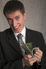 young successful businessman with money on the gray