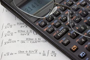 Scientific calculator , reading glasses against math text book