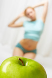 The apple in the foreground, on a background the young girl poster