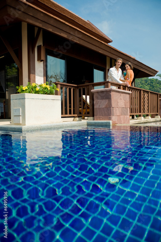 Young attractive couple standing by their pool villa with drinks