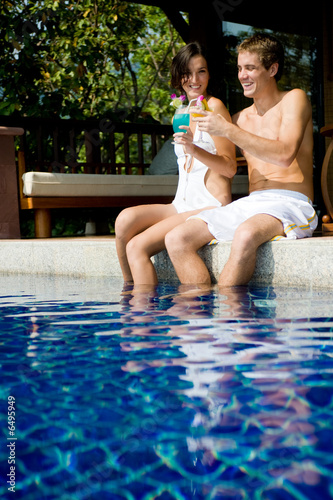 Young attractive couple sitting poolside with tropical cocktails