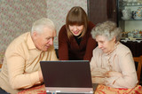 grandparents and granddaughter looking to the laptop poster