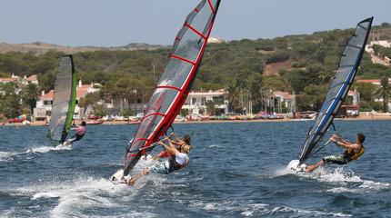 Group of windsurfers racing towards the shore