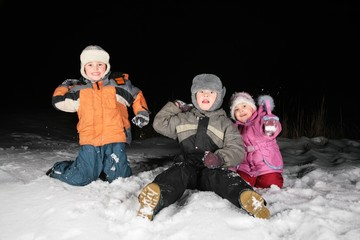 children play snowblls in the night