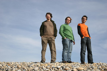 3 young men posing at the beach