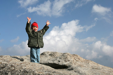 Young kid on top of the mountain