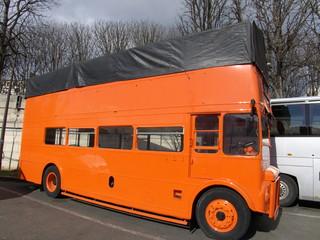 Bus orange à étage avec toit bâché de tissu noir.