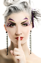Beautiful woman with artistic make-up asks to keep silence