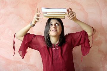 ragazza con 4 libri appoggiati sulla testa