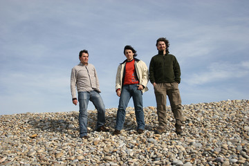 3 young men posing at the beach