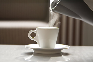 Hot water flowing from a teapot in a white cup