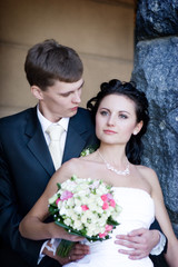 a portrait of the groom and the bride by the stone wall
