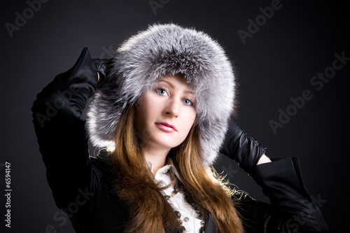 poster of Young woman in fluffy cap.