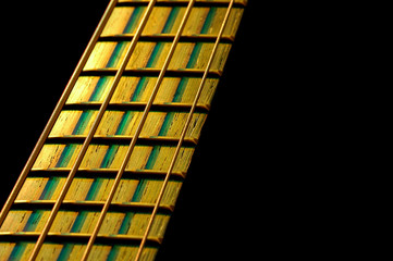 bass guitar fretboard under stage lighting on black