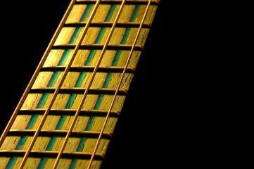 bass guitar fretboard under stage lighting on black