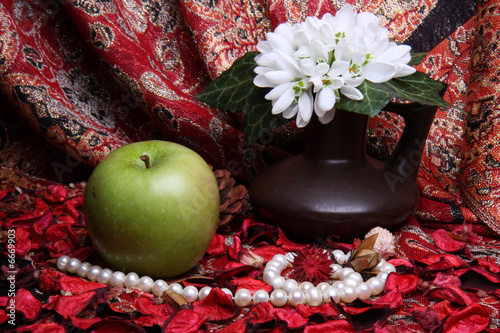 Still life with apple, flowers and pearls