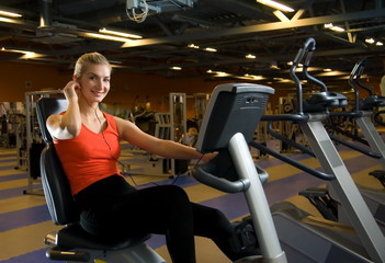 Beautiful young woman doing exercise in a gym while listening to