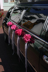 Black wedding limousine with flowers on side